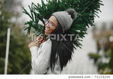 African woman choosing a christmas tree 73129200