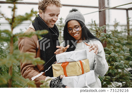 Mixed couple standing with gifts by the Christmas tree 73129216