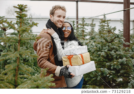 Mixed couple standing with gifts by the Christmas tree 73129218