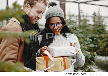 Mixed couple standing with gifts by the Christmas tree 73129220