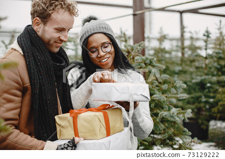 Mixed couple standing with gifts by the Christmas tree 73129222