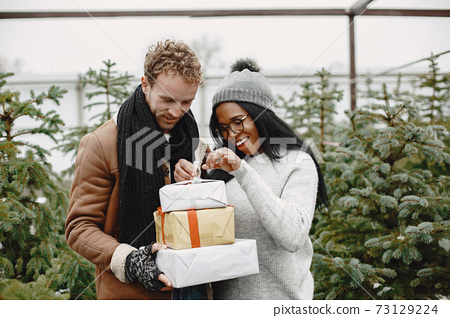 Mixed couple standing with gifts by the Christmas tree 73129224