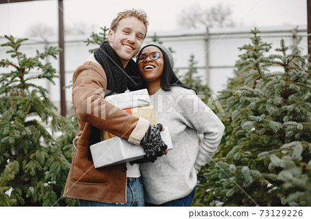 Mixed couple standing with gifts by the Christmas tree 73129226