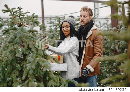 Mixed couple standing with gifts by the Christmas tree 73129232