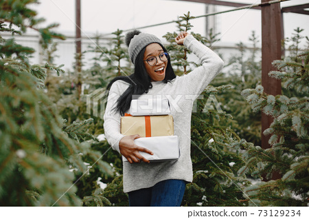 African woman choosing a christmas tree 73129234
