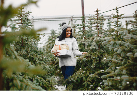 African woman choosing a christmas tree 73129236