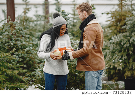 Mixed couple standing with gifts by the Christmas tree 73129238
