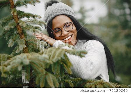 African woman choosing a christmas tree 73129246