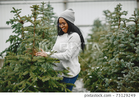 African woman choosing a christmas tree 73129249