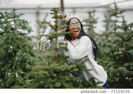 African woman choosing a christmas tree 73129250