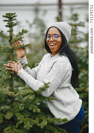 African woman choosing a christmas tree 73129252