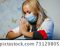 Exhausted female doctor in medical mask praying during home visit 73129805