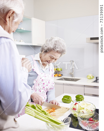 happy senior asian couple preparing meal together in kitchen 73139991