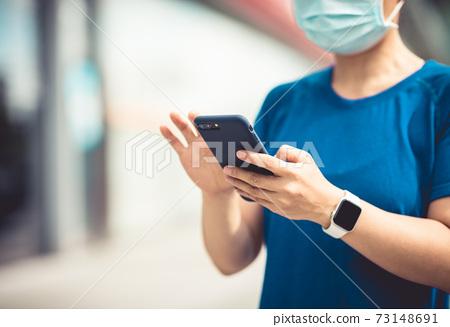 Woman using smart phone on city 73148691
