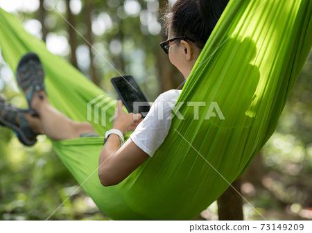 Relaxing in hammock hand using smartphone in tropical rainforest 73149209