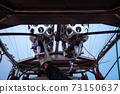 Hot air balloon pilot has his hand on the gas burner. 73150637