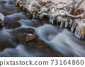 Clear stream and icicles in winter 73164860