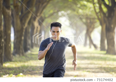 Asian young Man running in the forest on  foggy at  morning 73174402
