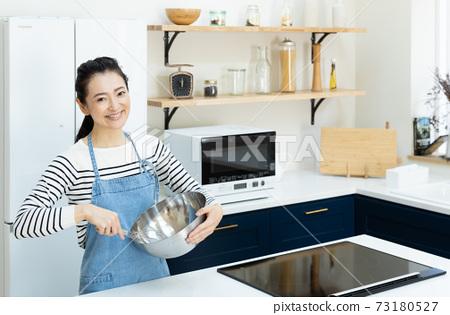 站立在廚房裡的中間婦女 73180527