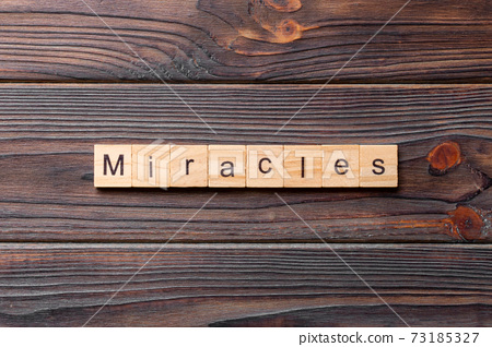 miracles word written on wood block. miracles text on cement table for your desing, concept 73185327