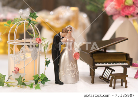 Miniature wedding couple doll with piano simulation wedding decoration on white table 73185987
