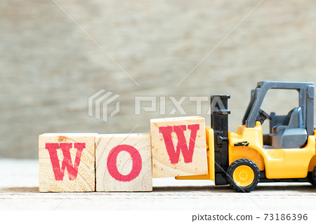 Toy forklift hold letter block w to complete word wow on wood background 73186396