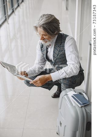 Senior businessman with travel suitcase in airport 73187343