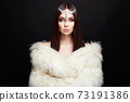 Beautiful woman with jewelry crown on her head and fur 73191386