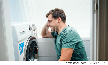Portrait of young man struggling and getting confused while setting washing machine for laundry 73214073
