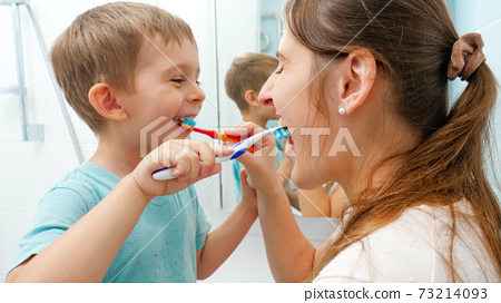 Smiling little boy with young mother brushing teeth and cleaning mouth with toothbrushes to each other. Family having fun while taking care of teeth hygiene and healthcare 73214093