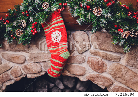 Christmas stockings hanging over a fireplace with candles on the mantlepiece. 73216694