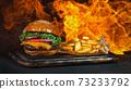 Tasty cheeseburgers, lying on vintage wooden cutting board. 73233792