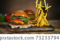 French fries fall next to cheeseburger, lying on vintage wooden cutting board. 73233794