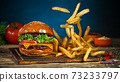 French fries fall next to cheeseburger, lying on vintage wooden cutting board. 73233797