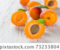 Fresh apricots on wooden table 73233804