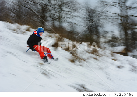 the boy descends from the hills in the sled, the movement is blurred 73235466