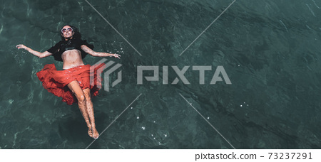 Aerial view of a woman in the sea 73237291