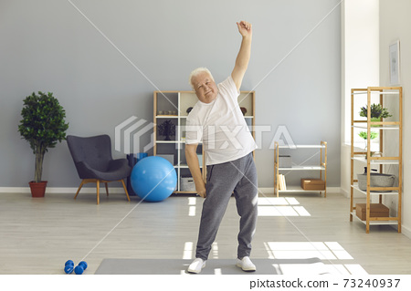 Positive mature man in home sportswear doing light exercises at home or in a rehab center. 73240937