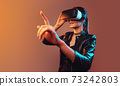 Young girl getting experience VR headset is using augmented reality eyeglasses being in virtual reality. Girl with hands up wearing virtual reality goggles. Woman touching air during VR experience 73242803