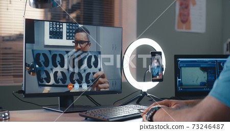 Mature doctor showing X ray to crop colleague during online seminar 73246487