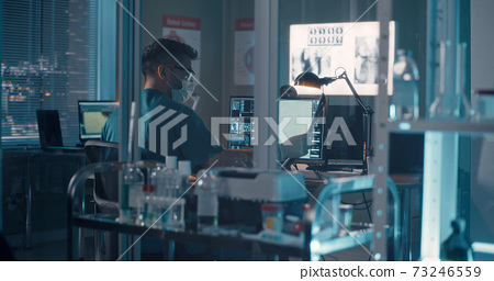 Doctor using computer in lab 73246559