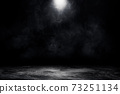 Studio dark room concrete floor grunge texture background with spot lighting and fog or mist in black background. 73251134
