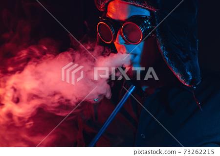 futuristic cyberpunk portrait of a man smoking a shisha hookah and blowing a cloud of smoke 73262215