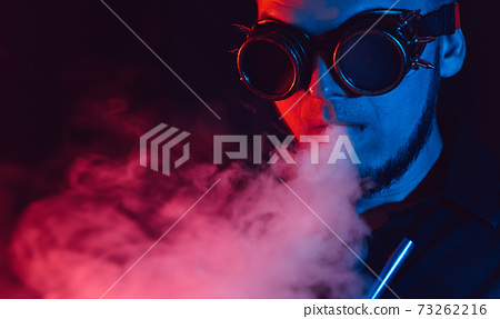 portrait of man in futuristic glasses smokes a hookah and blows a cloud of smoke in a shisha bar 73262216