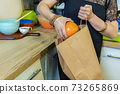 Woman take out fruits from paper bag 73265869