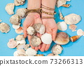 Woman holding shells in her hands 73266313