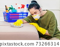 Woman in protective face mask cleaning sofa 73266314