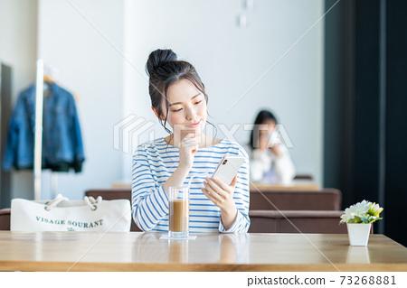 一個年輕的女人,看著在一家咖啡館的智能手機 73268881