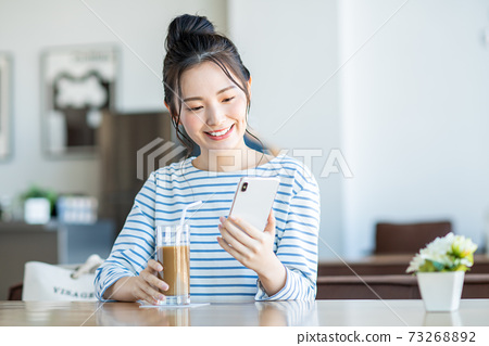 A young woman watching a smartphone in a cafe 73268892