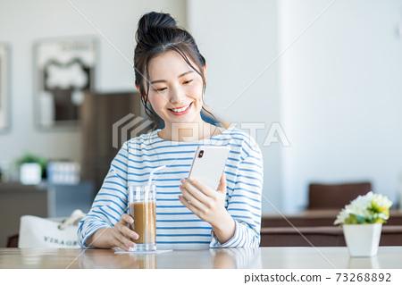 一個年輕的女人,看著在一家咖啡館的智能手機 73268892